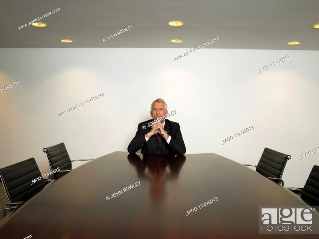 Stock Photo: Businessman sitting alone in conference room.