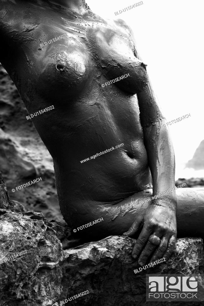 Stock Photo: Young adult Caucasian female nude sitting on rocky coast.