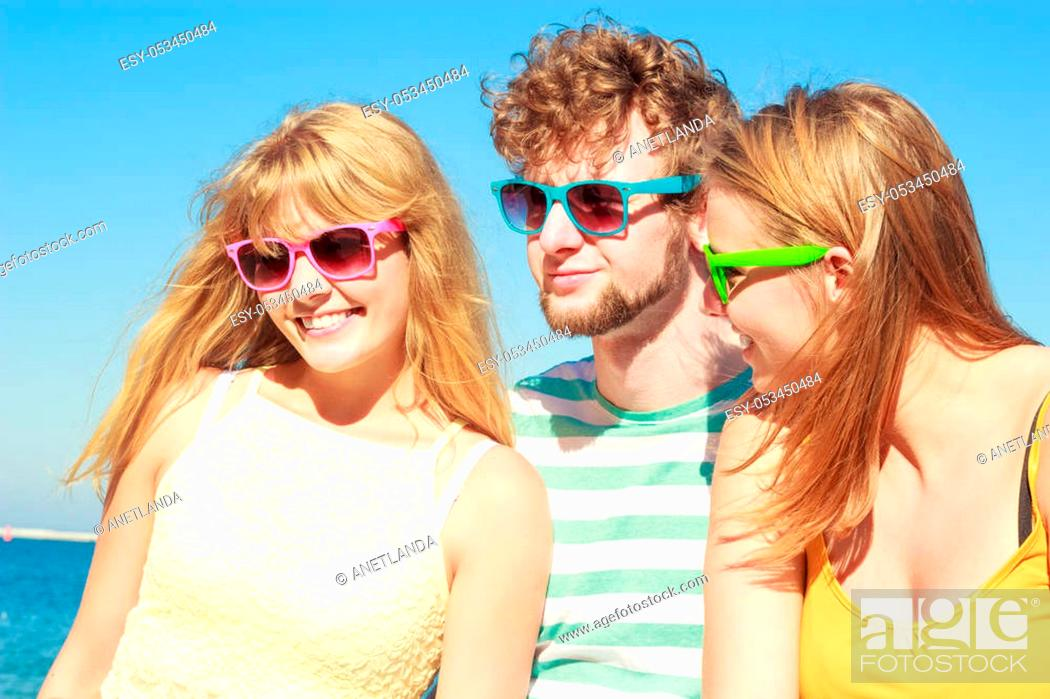 Stock Photo: Friendship happiness summer holidays concept. Group of friends boy two girls in colorful sunglasses having fun outdoor against sky, joy playful mood.