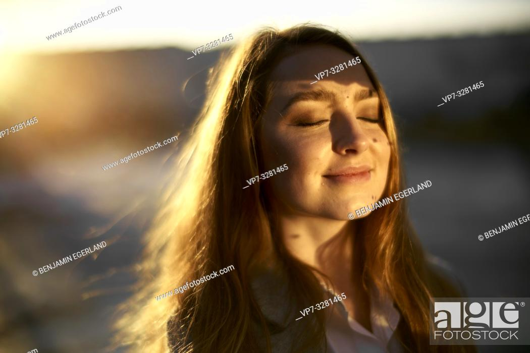 Imagen: young content woman outdoors enjoying warm sunlight, closed eyes, in Cottbus, Brandenburg, Germany.