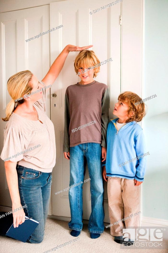 Stock Photo: Mother measuring her sons at home.