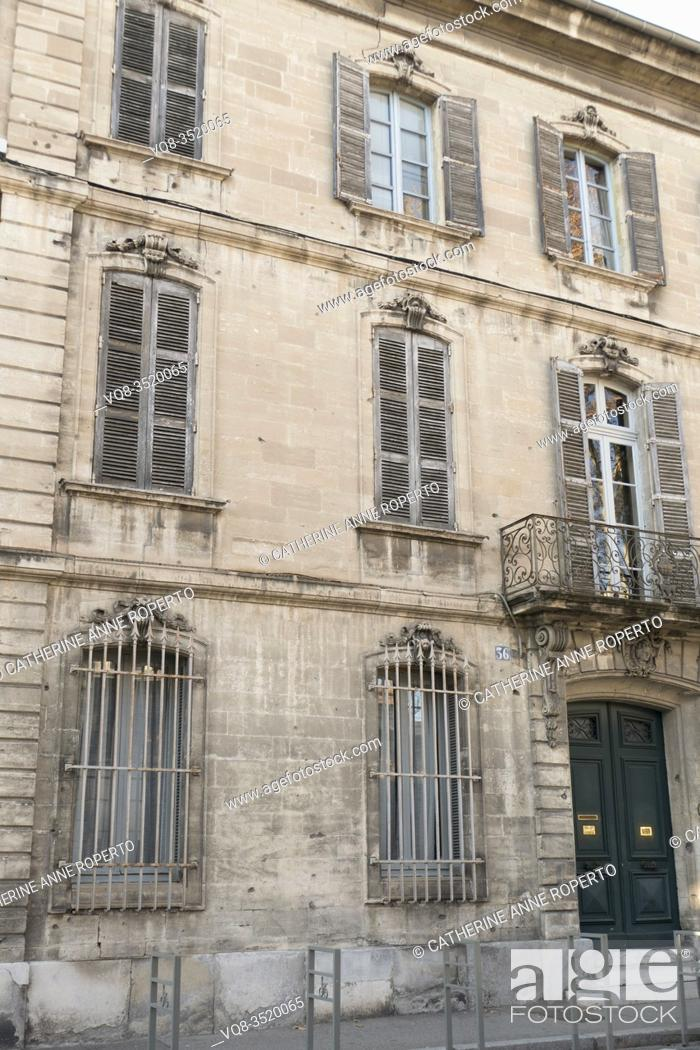 Stock Photo: Mellow stone classical facade of grand town house with pale blue sun weathered traditional shutters and decorative metal work balcony and grilles, Avignon.