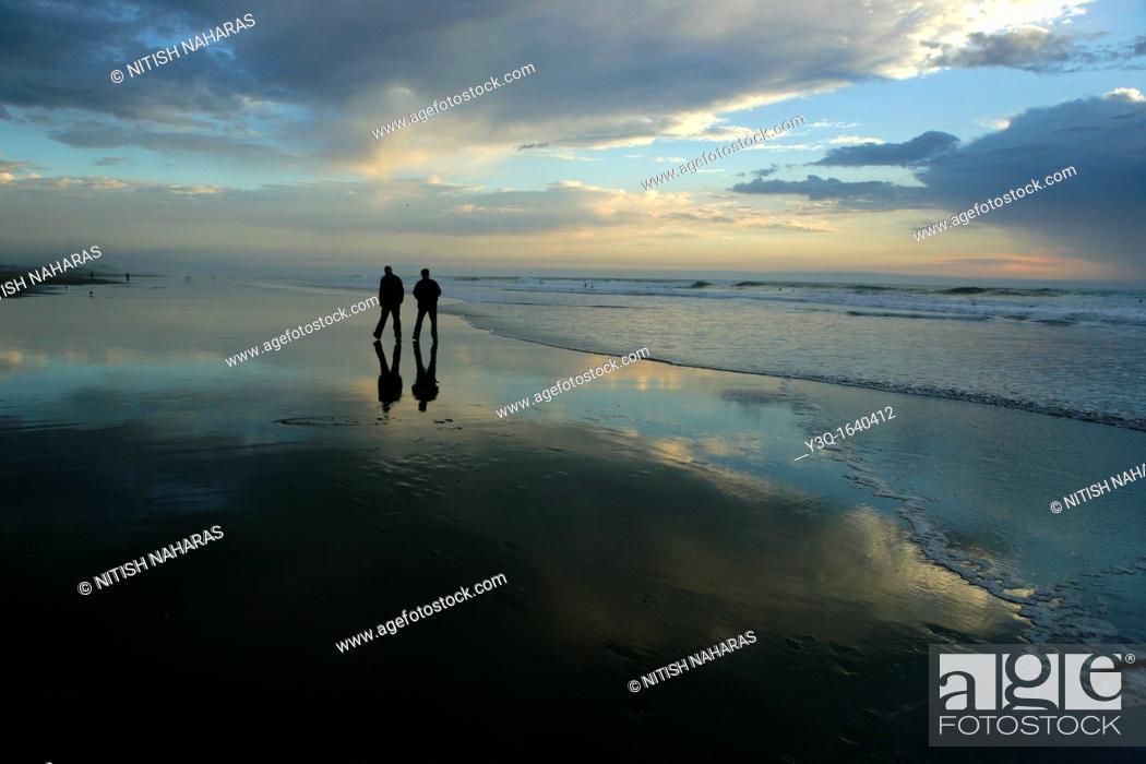 Stock Photo: A leisurely walk at dusk along the beach in San Francisco, California, USA.