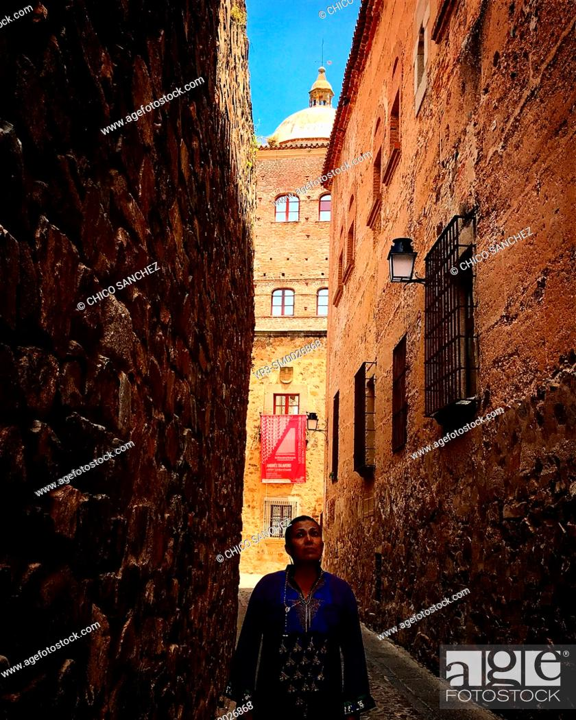 Stock Photo: A woman walks in a narrow street of the medieval city of Caceres, Extremadura. The tower of the Toledo-Moctezuma palace is seen in the back.