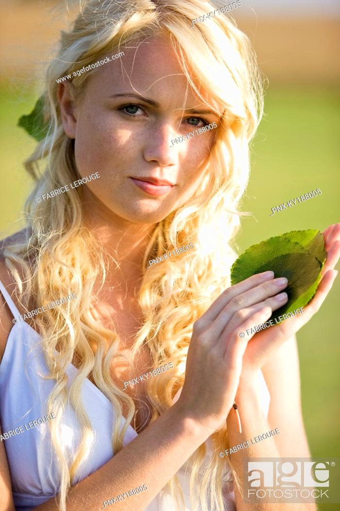 Stock Photo: Young woman holding green leaves.