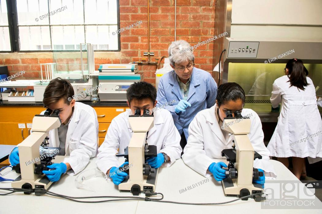 Stock Photo: Teacher and students working in science lab.