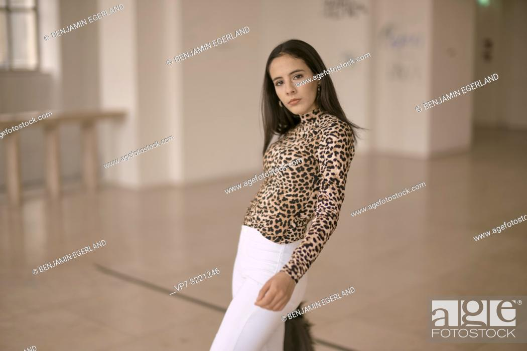 Stock Photo: confident woman indoors, fashionable clothing style, in Munich, Germany.