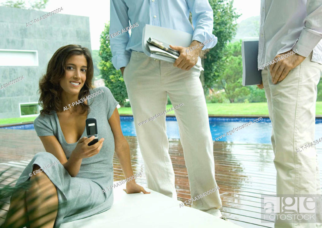 Stock Photo: Casually dressed young executives working near edge of pool.