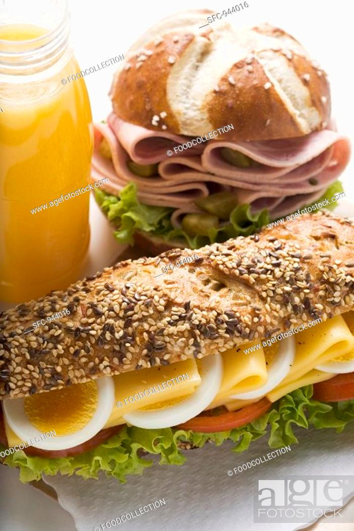 Stock Photo: Cheese sandwich, sausage in lye roll and fruit juice.