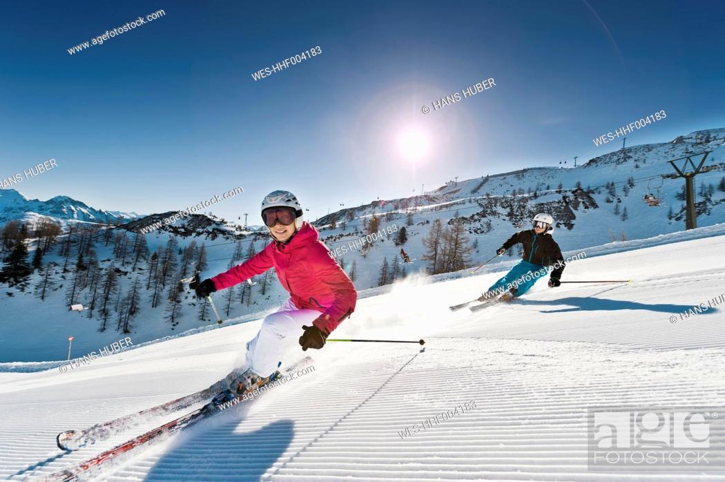 Stock Photo: Austria, Salzburg, Young couple skiing on mountain.