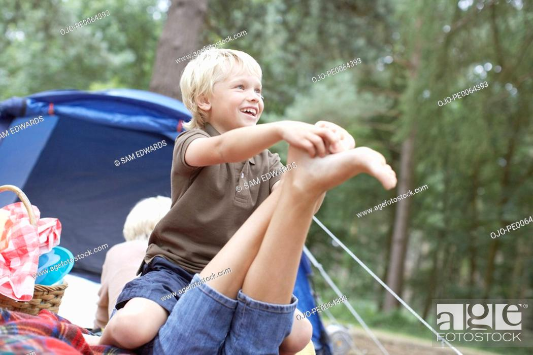 Stock Photo: Son tickling mothers foot in campsite.