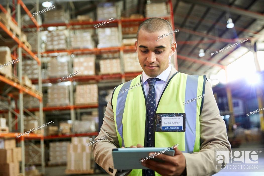 Stock Photo: Manager using digital tablet in distribution warehouse.