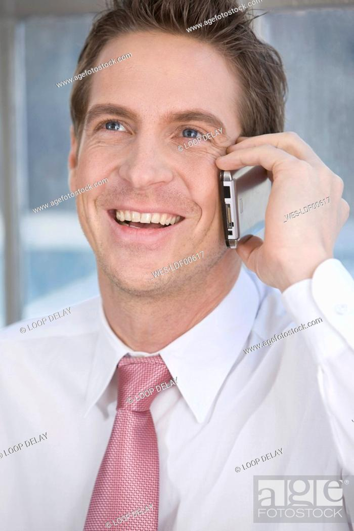 Stock Photo: Germany, Munich, business man using mobile phone, smiling, portrait.