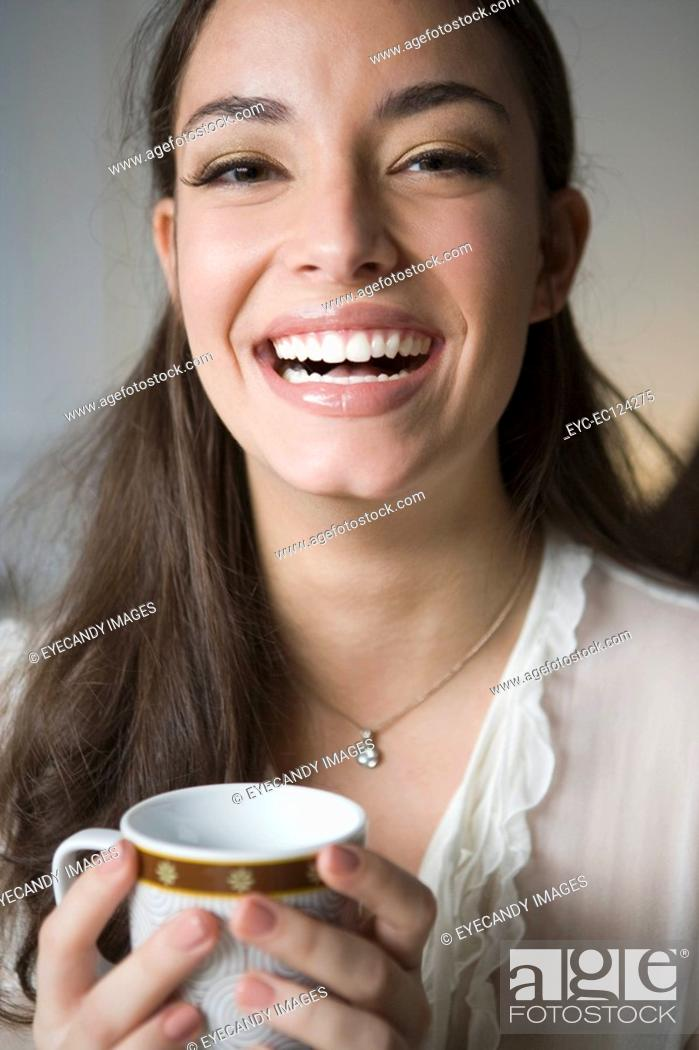 Stock Photo: Portrait of a cheerful young woman holding tea cup.