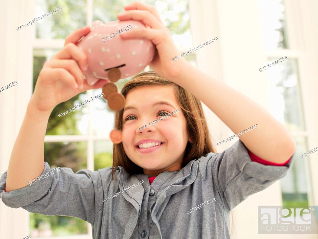 Stock Photo: Excited girl emptying coins from piggy bank.