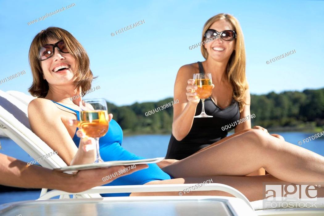 Stock Photo: Women having drinks on lounge chairs.