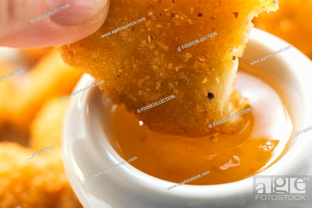 Stock Photo: Dipping a chicken nugget in apricot sauce.
