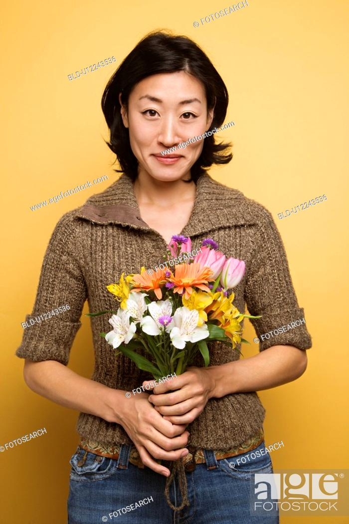 Stock Photo: Woman holding bouquet of flowers.