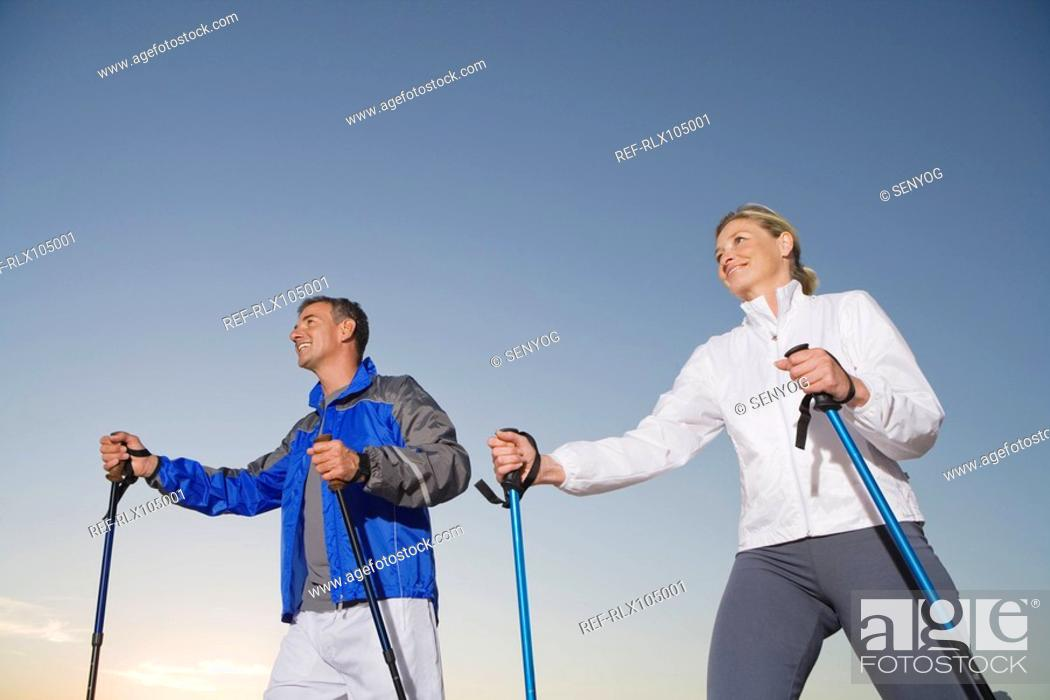 Stock Photo: Senior couple wearing tracksuit doing Nordic Walking at sunset.