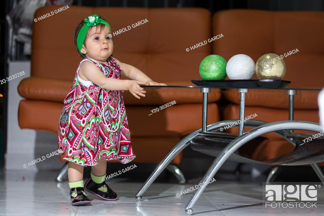 Imagen: Girl playing with colorful balls in a living room.