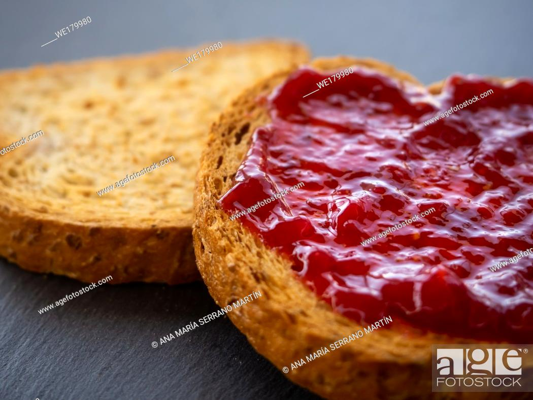Imagen: Two slices of toast with raspberry jam on a slate plate.