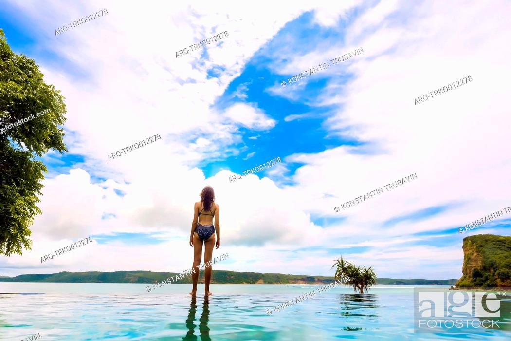 Imagen: Rear view of woman in bikini standing on lakeshore against white clouds.