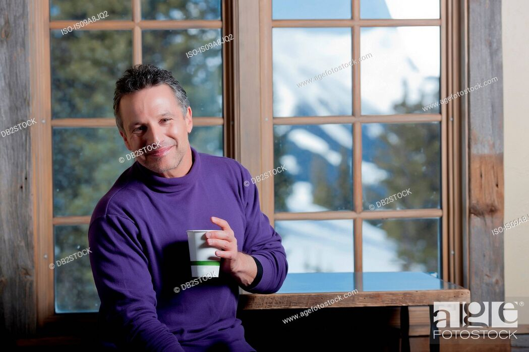 Stock Photo: Mature man holding hot drink indoors, smiling.