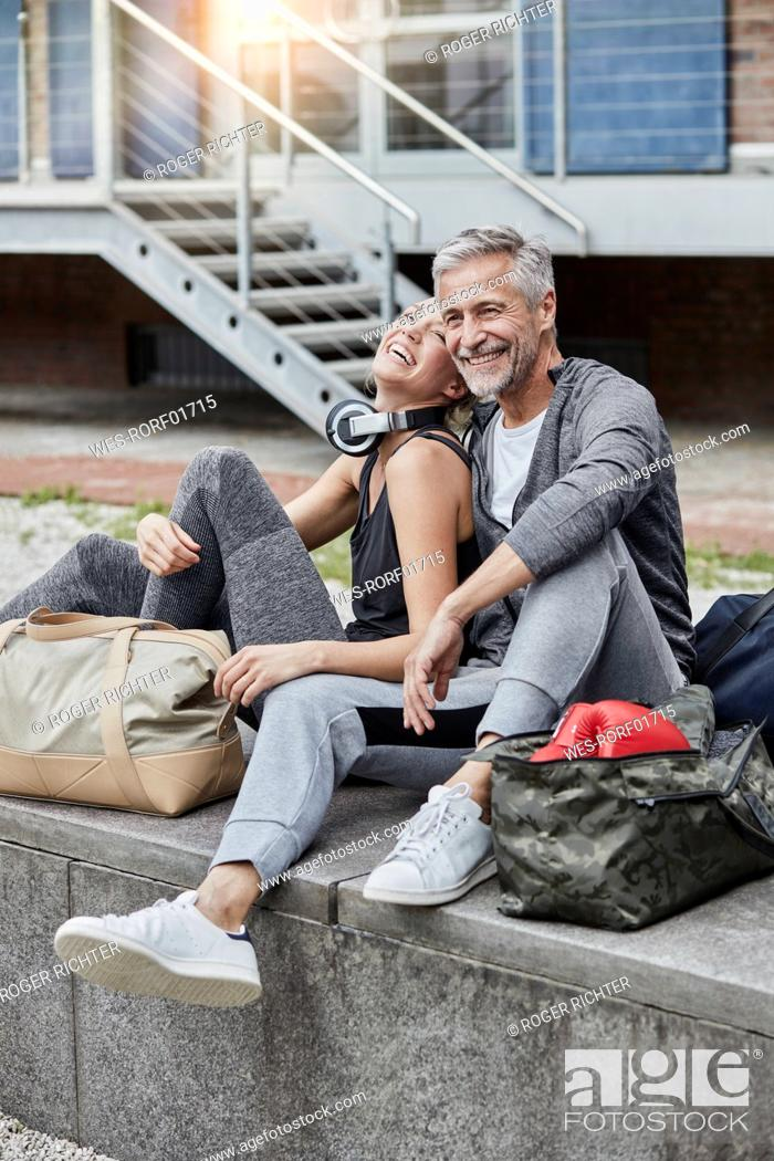 Stock Photo: Laughing mature man and young woman with sports bag sitting in front of gym.