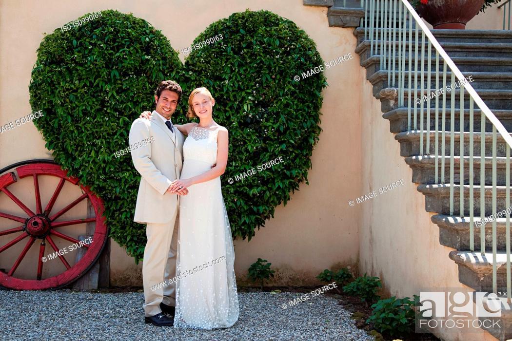 Stock Photo: Newlyweds by heart shaped bush.