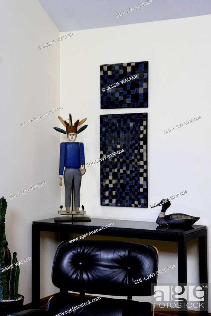 Stock Photo: LIVING ROOMS, contemporary room with new and antique folk art Amish denim quilt pieces duck decoy, figural sculpture, partial Eames chair.
