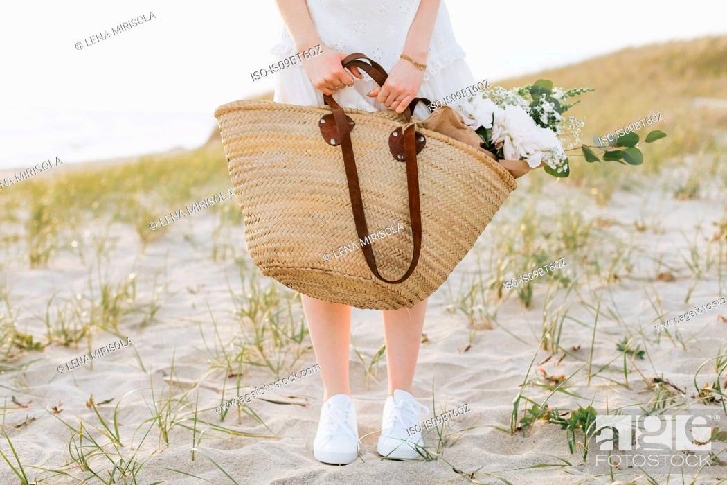 Stock Photo: Young woman carrying shoulder bag with flowers on coastal dunes, waist down, Menemsha, Martha's Vineyard, Massachusetts, USA.
