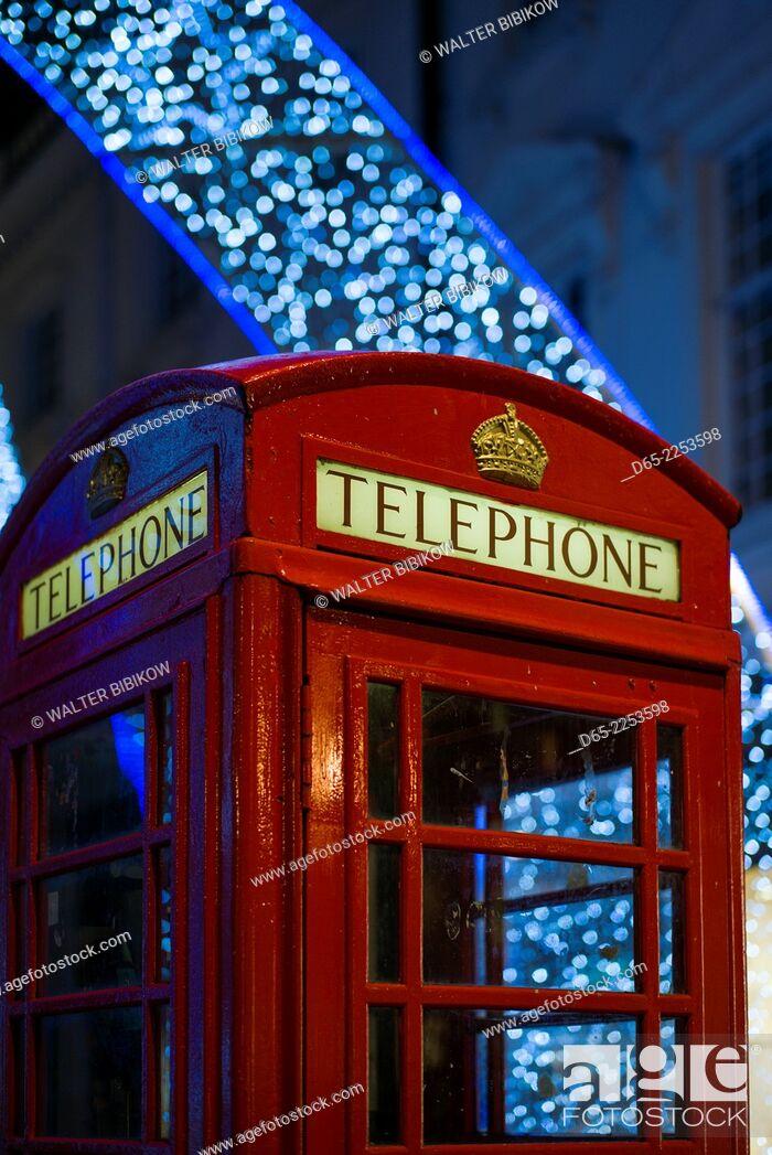 Stock Photo: England, London, Soho, English telephone box and Christmas decorations.