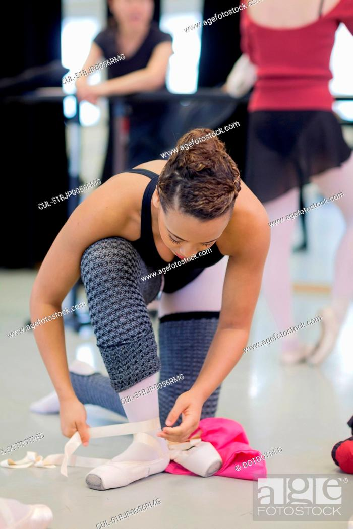 Photo de stock: Ballet dancer tying on pointe shoes.