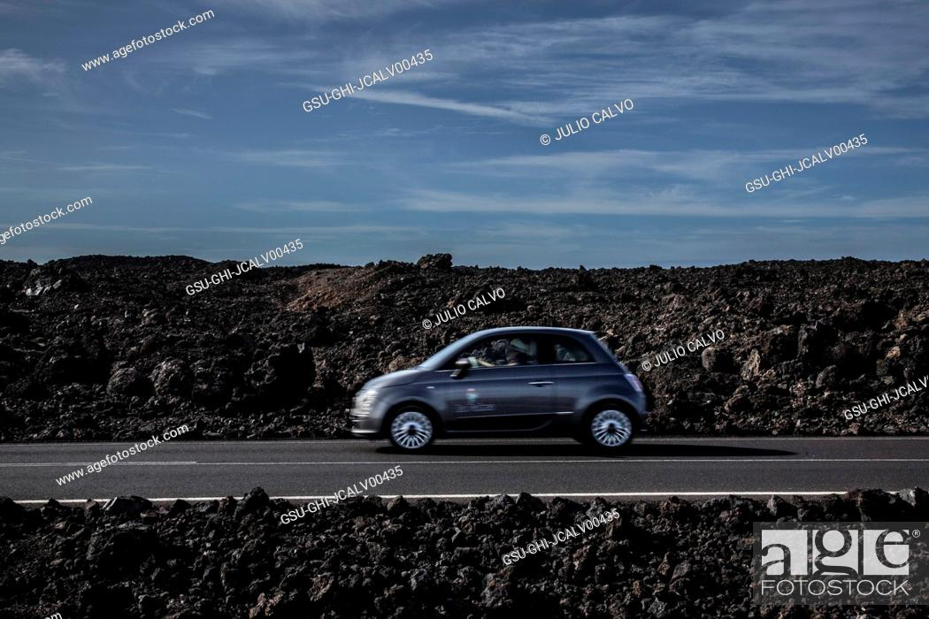 Stock Photo: Car on Road Against Rocky Landscape.