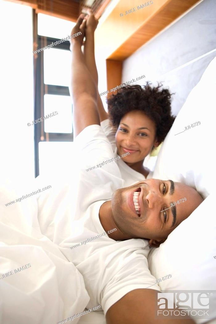 Stock Photo: Young couple lying in bed, holding hands and smiling, portrait.