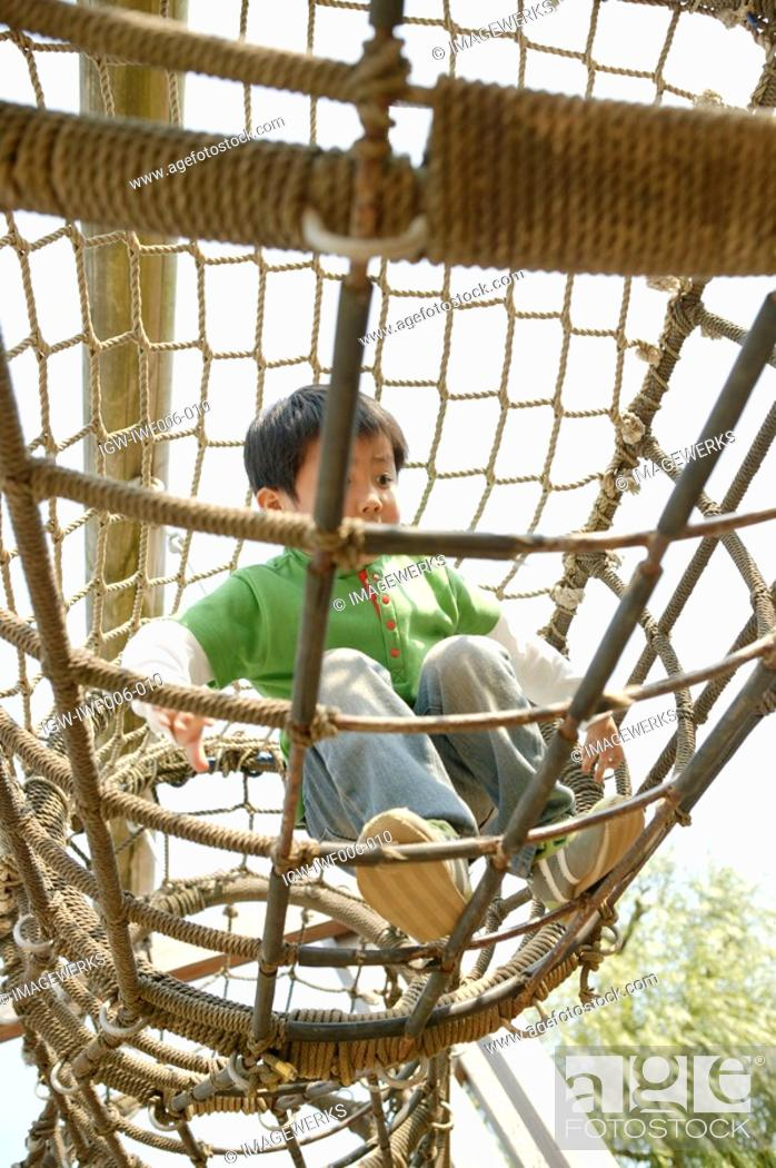 Stock Photo: A small boy enjoying the movement in the netted cage.
