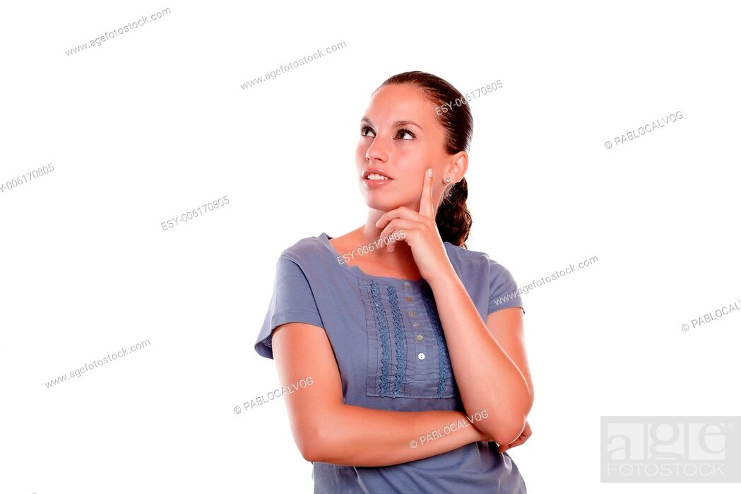 Stock Photo: Reflective young female looking to her right up on blue blouse on isolated background - copyspace.