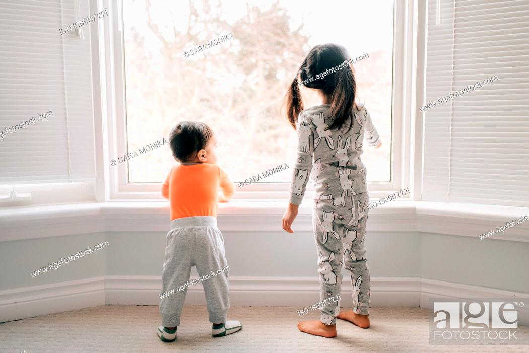 Photo de stock: Girl and baby brother looking through living room window, rear view.