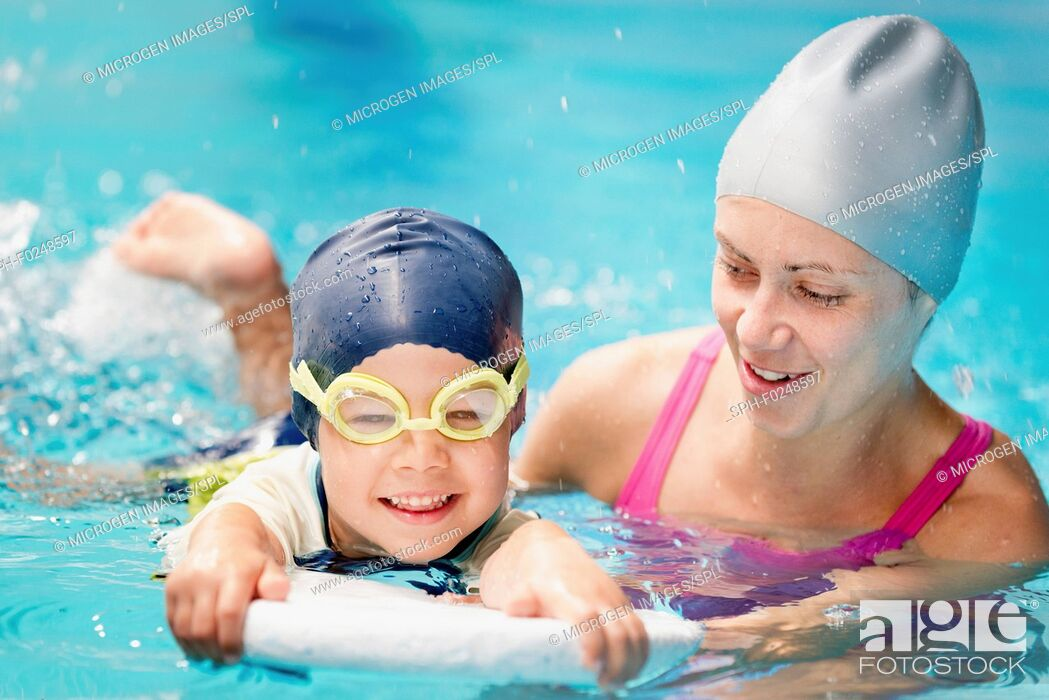 Stock Photo: Little boy learning to swim with instructor's help.