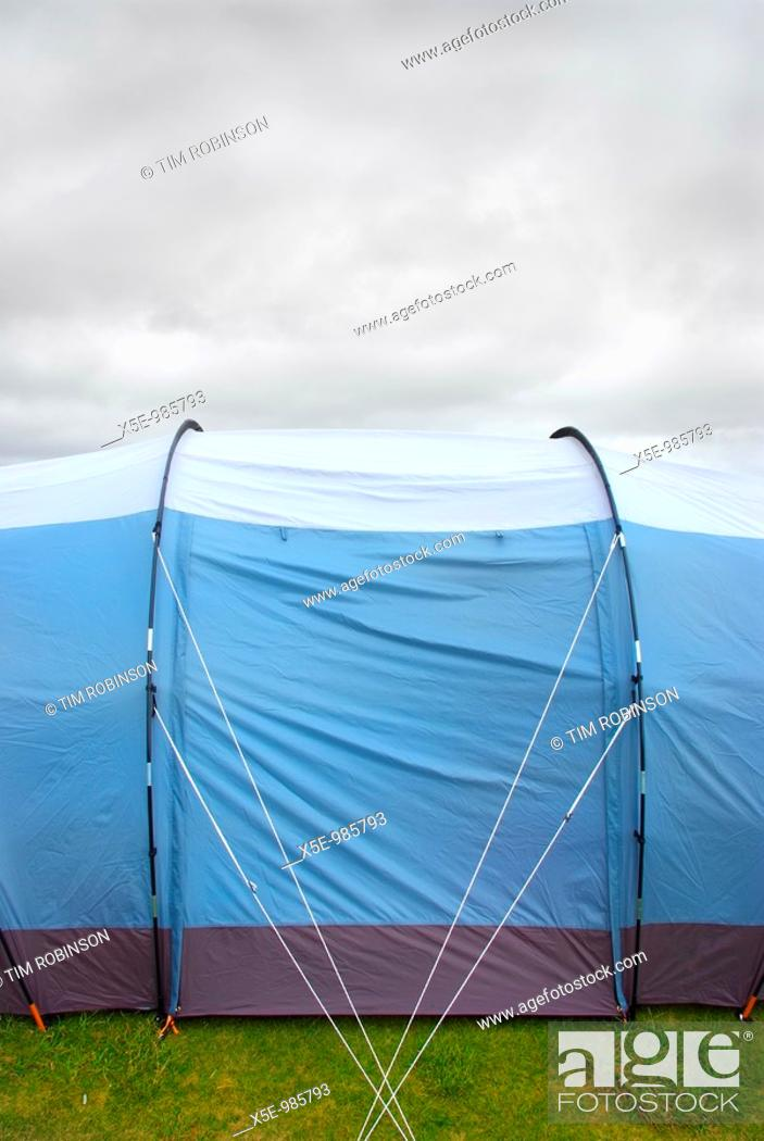 Stock Photo: Side view of blue tent under overcast grey sky.