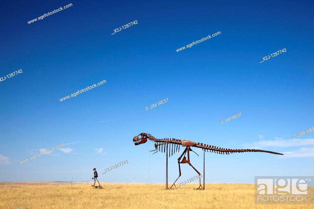 Stock Photo: Stamford, South Dakota - Skeletons of a man and a dinosaur walking across the plains of South Dakota.