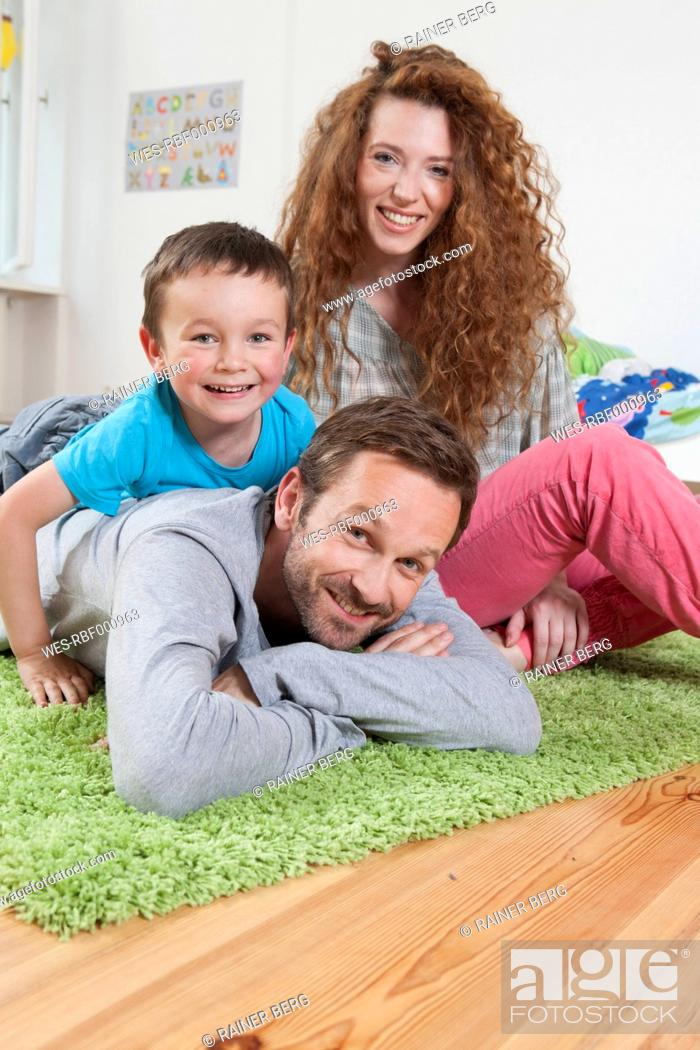 Stock Photo: Germany, Berlin, Family lying on floor, smiling, portrait.