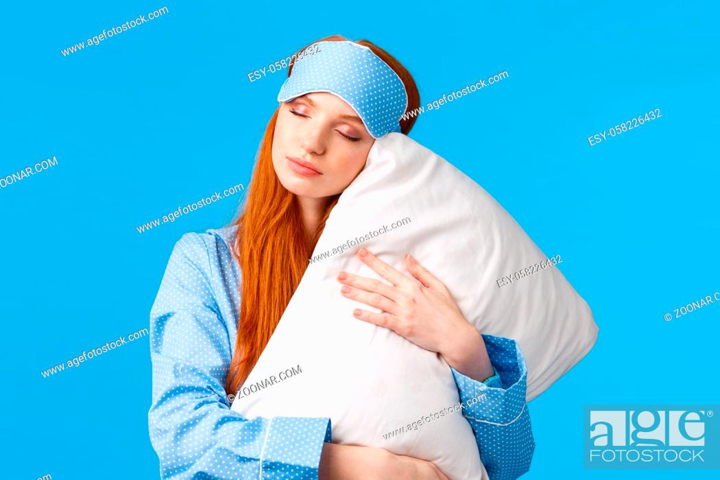 Stock Photo: Beauty, female and lifestyle concept. Relaxed and relieved lovely redhead woman in sleep mask and pyjama, close eyes sleepy, having sweet dreams, hugging pillow.