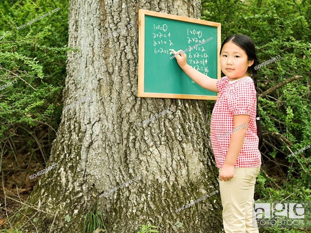 Stock Photo: A girl writing on a blackboard.
