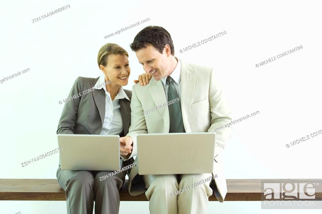 Stock Photo: Male and female business associates, both using laptop computers, man pointing to woman's screen.