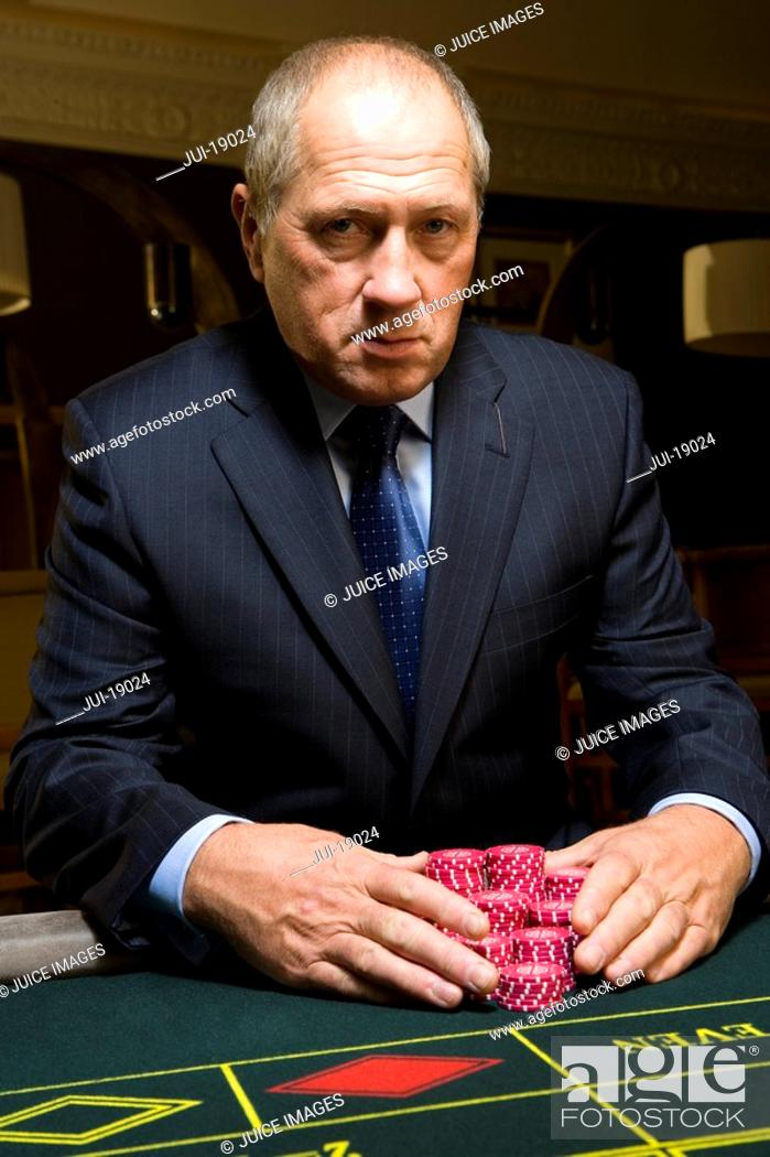 Stock Photo: Mature man with gambling chips at roulette table, portrait.