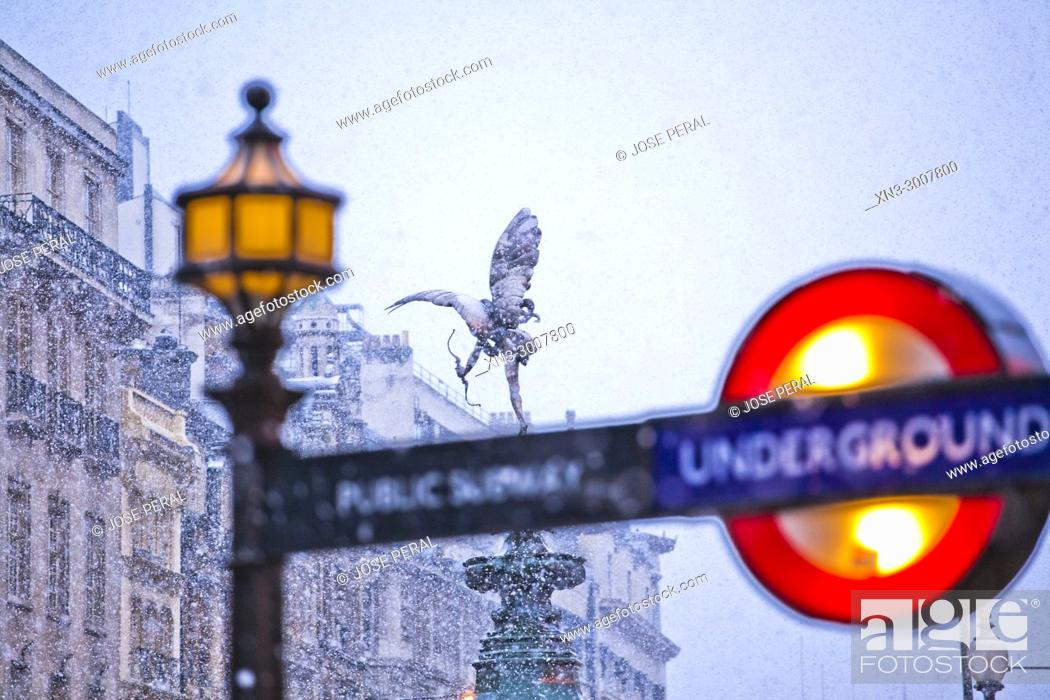 Stock Photo: Snowing, Underground sign, Subway, on background The Angel of Christian Charity, Anteros, on Shaftesbury Memorial Fountain, by Alfred Gilbert, Piccadilly Circus.