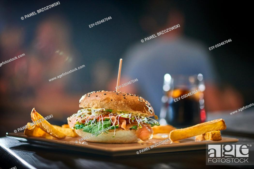 Stock Photo: Salmon burger with wooden spike served with french fries. Blurred pub background. Copy space.