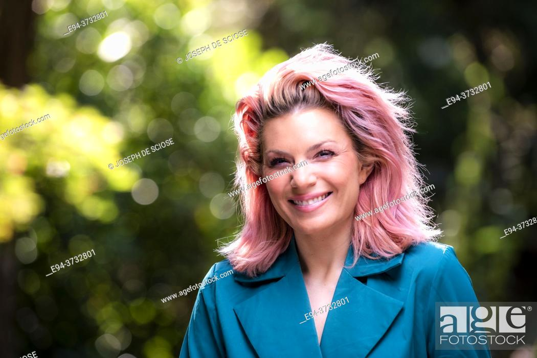 Stock Photo: A smiling 34 year old blond woman looking at the camera, outdoors.