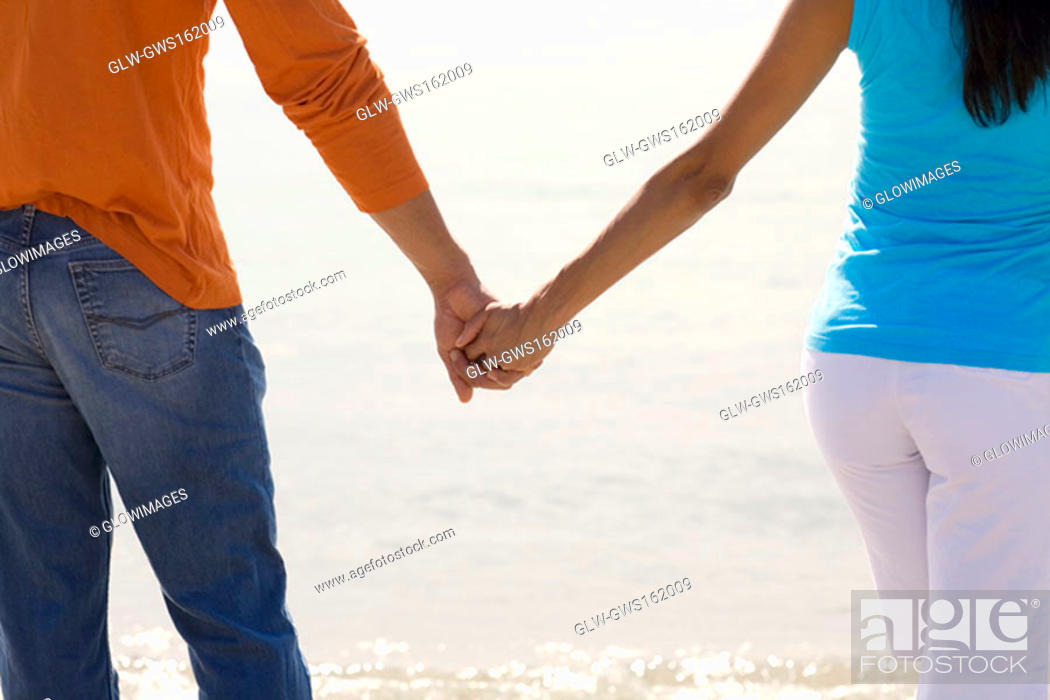 Stock Photo: Mid section view of a young couple standing on the beach and holding hands.